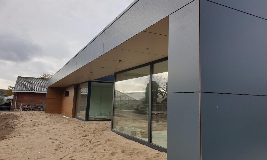 Grote moderne overkappen en tevens zonwering in combinatie met veel glas tijdens bouwwerkzaamheden